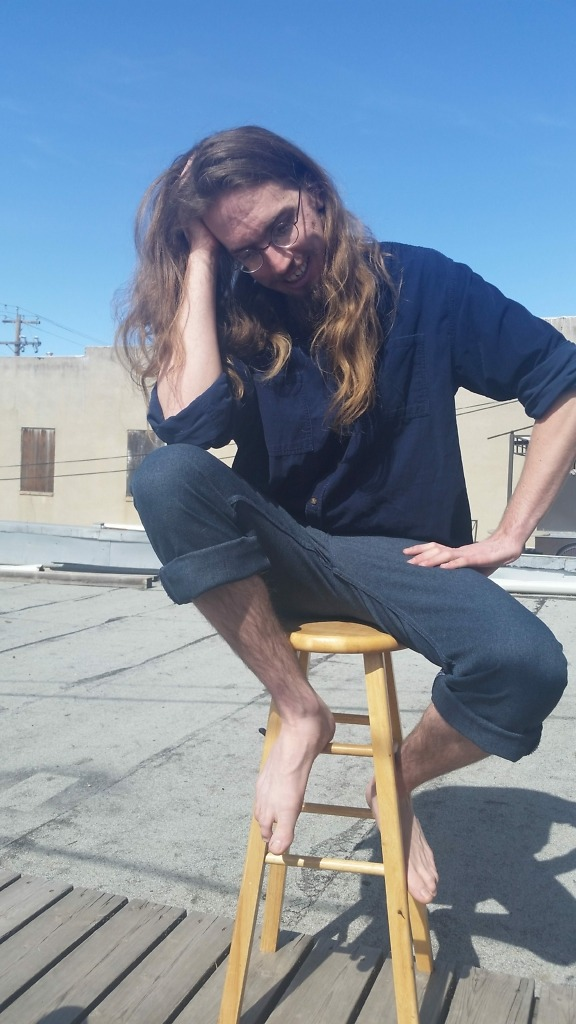 A photo of Jake sitting on a stool with in front of a blue sky, barefoot and looking down with a smile.